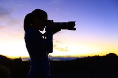 Photographer taking pictures with SLR camera. At night. Nature landscape photographer with telephoto lens. Silhouette of woman taking photo after sunset Stock Images