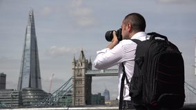 Photographer taking pictures of Tower Bridge and Shard in London stock footage