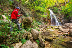 The photographer taking pictures of waterfall Stock Image