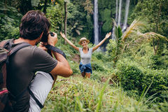 Photographer taking pictures of a woman by waterfall. Male photographer taking pictures of a young women standing in front of waterfall in forest. Couple Royalty Free Stock Images