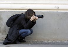 Photographer taking a shoot. With a digital camera and a tele lens Royalty Free Stock Photo