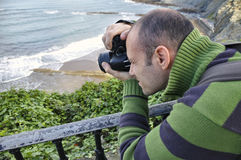 Photographer taking a snapshot of a beach Stock Image