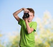 Photographer. Teenage boy using professional camera outdoors. Royalty Free Stock Photography