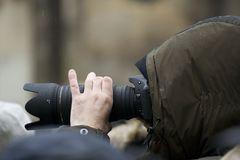 Photographer with telephoto lens. Photographer taking a shoot with a digital camera and a telephoto lens Royalty Free Stock Images