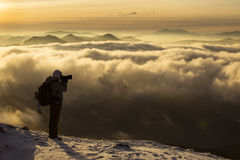 Photographer on top of mountain over the clouds enjoying the vie Royalty Free Stock Photos