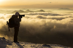 Photographer on top of mountain over the clouds enjoying the vie Stock Image