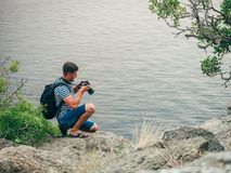 Photographer tourist man looking at the screen digital SLR professional camera. With a backpack on a rock stock images