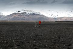 Photographer tourist stands in the mountains and from a tripod t. Akes pictures of the landscape of Iceland Royalty Free Stock Photo