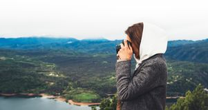 Photographer tourist traveler standing on green top on mountain holding in hands digital photo camera, hiker taking click photogra. Phy, girl enjoy nature stock image