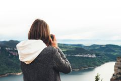 Photographer tourist traveler standing on green top on mountain holding in hands digital photo camera, hiker view from back taking royalty free stock photography