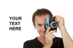 Photographer with a toy camera. Smiling male photographer with a toy camera on a while background with space for text copy Stock Photo