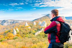Photographer traveler with a backpack admiring the beautiful mountains in autumn stock image