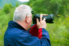 Photographer the traveler behind filming photos Royalty Free Stock Image