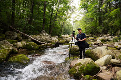 Photographer traveler on a mountain river Stock Images