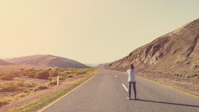 Photographer traveler on the road in mountains stock photo