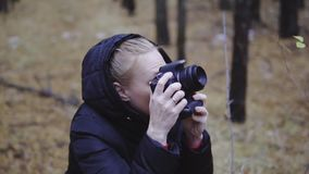 Photographer traveler takes pictures of nature in the autumn forest. cinematic shot, slow-motion shooting. Photographer traveler takes pictures of nature in the stock video footage