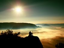 Photographer with tripod and camera on cliff and thinking. Dreamy fogy landscape Stock Images