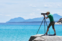 Photographer with tripod shooting sea landscape Stock Photography
