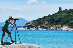 Photographer with tripod shooting sea landscape Stock Image