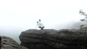 Photographer with tripod standing on rocky view point and taking photos of misty morning landscape. National park Saxon Switzerlan stock video footage