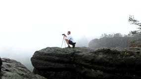 Photographer with tripod standing on rocky view point and taking photos of misty morning landscape. National park Saxon Switzerlan stock video