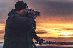Photographer with two cameras taking a shot of sunset from roof royalty free stock images
