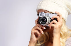 Photographer. Unrecognizable blonde young woman ta. King photo with vintage film camera in studio Royalty Free Stock Image