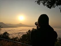 Photographer use DSLR camera to take a photo with fog on mountain. Landscape photography concept Stock Image