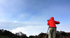 Photographer use tripod taking photo on mountain peak Royalty Free Stock Photography