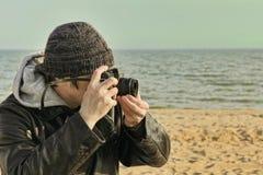Photographer using retro photo camera on sea beach. Royalty Free Stock Photo