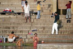 Photographer in Varanasi. India, Varanasi: photographer is taking a picture of ritual purification, that is a feature of hinduism. The aim of these rituals is to Stock Photos