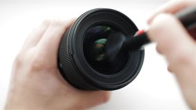 The photographer or videographer cleans front lens from dust and dirt at an angle with the help of a professional. Cleaning brush. Closeup shot stock video