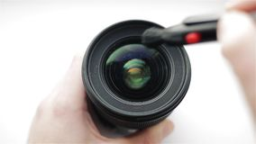 The photographer or videographer cleans front lens from dust and dirt with the help of a professional cleaning brush. The photographer or videographer cleaning stock video footage