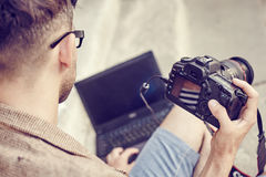 Photographer viewing photos on the camera. Young photographer viewing photos on the camera Royalty Free Stock Images