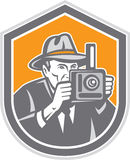 Photographer Vintage Camera Shield Retro. Illustration of a photographer wearing fedora hat shooting with vintage bellows camera set inside shield crest on Stock Images