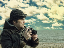 Photographer with vintage photo camera on sea beach. Royalty Free Stock Photography