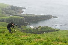 Photographer is waiting for the right shot on Mikines, Faroe Isl royalty free stock image