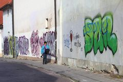 Photographer walks along graffiti walls in the Old town of Vilnius, Lithuania Royalty Free Stock Images
