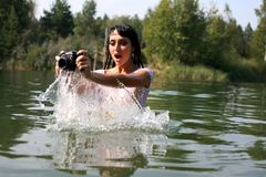Photographer in water. Lovely girl photographer in water in hot summertime Royalty Free Stock Photo