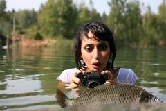 Photographer in water. Woman photographer in water with big fish Royalty Free Stock Photo