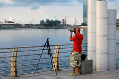 Photographer at waterfront in Singapore. Photographer making photos at waterfront in Singapore Stock Photo