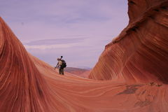 Photographer in Waves of Sandstone Stock Photo