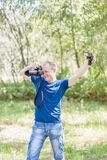 Photographer wearing blue t-shirt working outdoors. Summer day. Young man with a DSLR camera and light equipment in hands stock photography