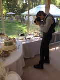 Photographer at a Wedding. Wedding Photographer in the process of shooting the dessert table stock image