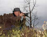 Photographer In The Wildflowers. World famous travel photographer Christian Heeb in the wildflowers on a stormy morning with his Nikon camera shooting royalty free stock photography