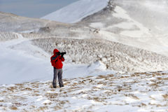 Photographer in winter mountain Royalty Free Stock Photo