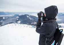 Photographer in the winter, on top of the mountain Stock Image