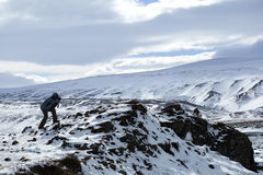 Photographer in wintry mountain landscape, Iceland Royalty Free Stock Image