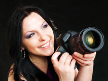 Photographer woman holding camera over dark. Smiling brunette photographer woman holding camera over dark background Stock Photography