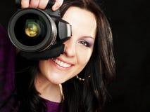 Photographer woman holding camera over dark. Smiling brunette photographer woman holding camera over dark background Stock Photo